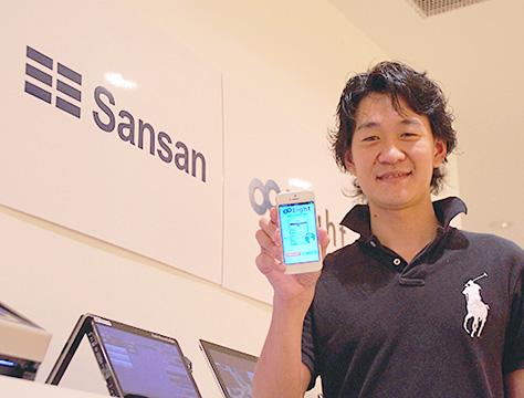 スマホを片手に持っているSansan  Eight 事業部マーケティングマネージャーの千住 氏の写真