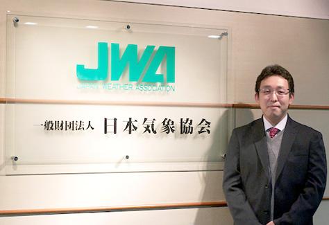 一般財団法人日本気象協会の看板の前に立つ 緒方氏の写真