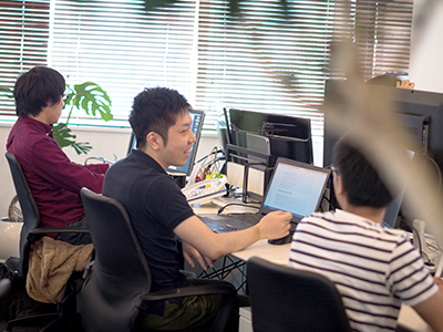 社員3人が横並びでPC作業をしている写真