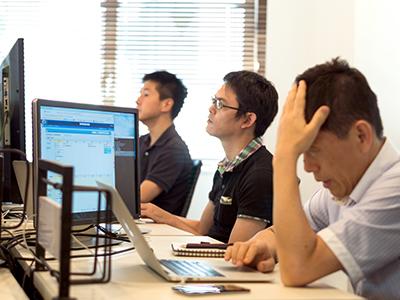 社員3人が横並びでPC操作をしている写真