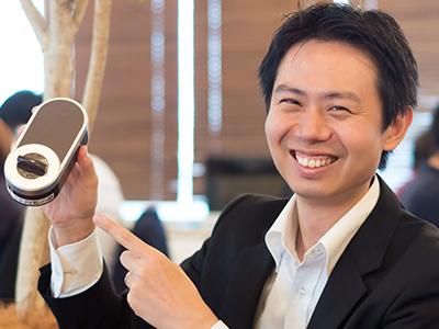 笑顔で端末を紹介している滝沢氏の写真