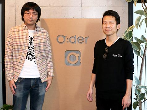 Oderロゴの前に立つ中野氏と石亀氏の写真