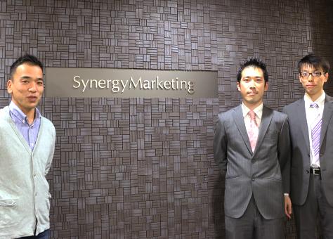 Synergy Marketingの受付の前で長谷川氏 長井氏 本多氏が立っている写真