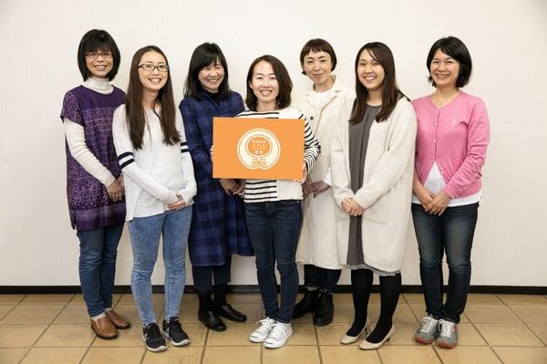 一般財団法人にんしんSOSの社員7人が横一列に笑顔で並んでる写真